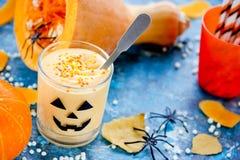 Crema batida poner crema de la calabaza en el vidrio adornado para Halloween Foto de archivo libre de regalías