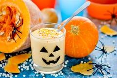 Crema batida poner crema de la calabaza en el vidrio adornado para Halloween Imágenes de archivo libres de regalías