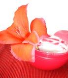 Crema cosmética con la flor roja Fotos de archivo libres de regalías