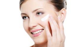 Crema cosmética de aplicación femenina bonita en cara Imágenes de archivo libres de regalías