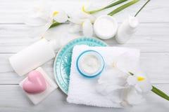 Crema cosmética en el tarro de cristal y otros accesorios del baño en de madera Imagen de archivo libre de regalías