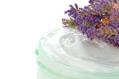 Crema cosmética en un tarro y flores de la lavanda Imagen de archivo