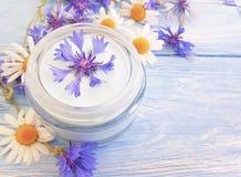 Crema cosmética, flor de la relajación de la higiene de la belleza de la manzanilla, aciano en un fondo de madera fotos de archivo libres de regalías