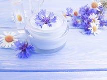 Crema cosmética, flor de la relajación de la higiene de la manzanilla, aciano en un fondo de madera fotos de archivo