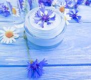 Crema cosmética, flor de la relajación de la manzanilla, aciano en un fondo de madera imagen de archivo
