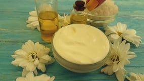 Crema cosmetica, fiore del crisantemo dell'olio su un fondo colorato video d archivio