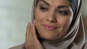 Crema de aplicación femenina árabe hermosa de la anti-edad en la cara, disfrutando de su aspecto almacen de video