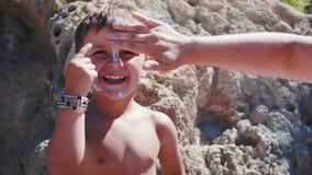 Crema de cara del ` s del muchacho del yeso de la mamá para la protección del sol almacen de video