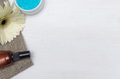 Crema de cara, flor blanca del gerbera y aceite esencial del azul Accesorios del baño Spa Terapia del aroma Imágenes de archivo libres de regalías