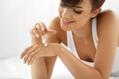 Crema de la mano de la mujer Ciérrese para arriba de la muchacha hermosa que aplica la loción Imagen de archivo