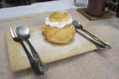 Crema dei choux della vaniglia sul piatto di legno immagini stock libere da diritti
