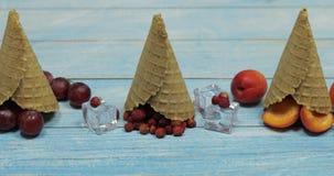 Crema del gelato alla frutta e della bacca Albicocca, fragola, ciliegia in un cono della cialda archivi video