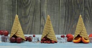 Crema del gelato alla frutta e della bacca Albicocca, fragola, uva in un cono della cialda video d archivio