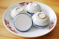 Crema del latte di cocco in 4 piccole tazze della porcellana nel piatto sulla tavola di legno Immagini Stock Libere da Diritti