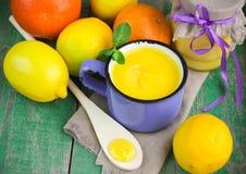 Crema del limone e limoni, arance e menta freschi sulla vecchia tavola di legno kurd Immagini Stock