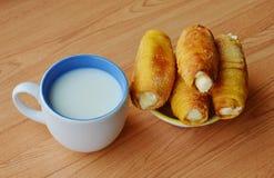 Crema del panino e tazza di riempimento del latte sulla tavola fotografia stock