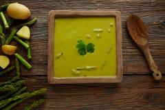Crema del verde de la sopa del espárrago en la tabla de madera envejecida Fotografía de archivo