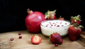 crema della frutta sul bordo di legno con il melograno ed altre fragole in un fondo scuro immagini stock libere da diritti