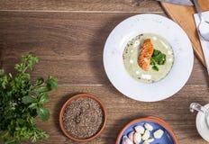Crema della minestra dei broccoli con la vista superiore di color salmone un fondo di legno Fotografie Stock