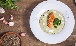 Crema della minestra dei broccoli con la vista superiore di color salmone un fondo di legno Fotografia Stock
