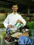 Crema di versamento del cuoco unico con salsa Fotografia Stock