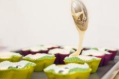 Crema di versamento del muffin nelle tazze del silicone del muffin Immagini Stock Libere da Diritti
