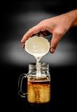 Crema di versamento nel vetro trasparente del caffè Fotografie Stock