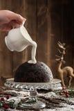 Crema di versamento sopra il budino di Natale Fotografia Stock Libera da Diritti