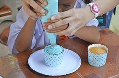 Crema dolce di goccia sul bigné Immagini Stock