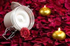 Crema e candele sui thepetals Fotografie Stock Libere da Diritti