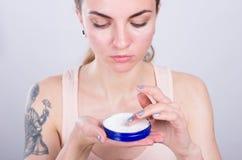 Crema hidratante facial del appliyng hermoso de la mujer joven Foto de archivo libre de regalías