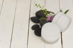 Crema igienica cosmetica di erbe con i fiori bianchi e rosa con roccia nera su fondo bianco di legno Vista superiore e fine su Fotografia Stock Libera da Diritti