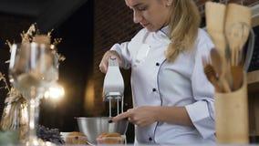 Crema mescolantesi dell'uovo bianco del confettiere femminile in ciotola facendo uso del miscelatore del motore stock footage