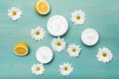 Crema naturale in contenitori, camomille e limone affettato sulla tavola di legno blu Fotografia Stock Libera da Diritti