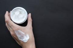Crema per il fronte o corpo in mano femminile Crema della sbavatura a disposizione Fotografia Stock Libera da Diritti