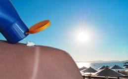 Crema per le solarizzazioni mentre la gente alla spiaggia immagine stock libera da diritti