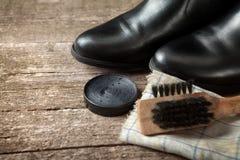 Crema polaca, botas negras, cepillo y paño Imagenes de archivo