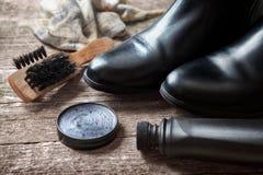 Crema polaca, botas negras, cepillo y pulidor Imagenes de archivo