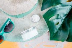 Crema y cosmético de la loción para la protección del sol en la opinión superior del fondo anaranjado Foto de archivo libre de regalías