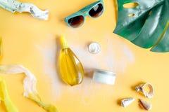 Crema y cosmético de la loción para la protección del sol en la opinión superior del fondo anaranjado Imagenes de archivo