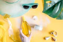 Crema y cosmético de la loción para la protección del sol en la opinión superior del fondo anaranjado Foto de archivo
