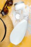Crema y cosmético de la loción para la protección del sol en la opinión superior del fondo anaranjado Fotos de archivo