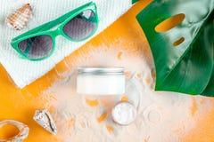 Crema y cosmético de la loción para la protección del sol en la opinión superior del fondo anaranjado Fotos de archivo libres de regalías