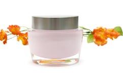 Crema y flor de la crema hidratante Foto de archivo libre de regalías