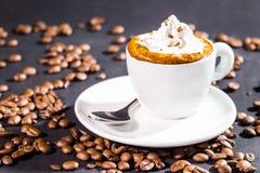 Crema y habas del top de la taza de café en un fondo negro Imagenes de archivo