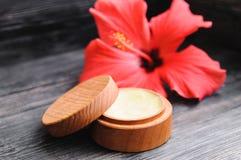 Crema y una flor rosada en un fondo de madera Imagen de archivo libre de regalías