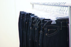 Cremagliere dei jeans che appendono in una memoria Fotografia Stock