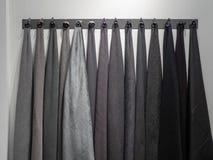 Cremalheira da parede com máscaras escuras de materiais cinzentos e pretos de telas da amostra fotografia de stock royalty free