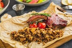 Cremalheira de entrecostos de porco assadas picantes do pimentão, trigo mourisco com cogumelo e tomates na placa de corte de made Imagens de Stock