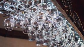 Cremalheira do metal com vidros limpos pequenos para o álcool nas fileiras no fundo de uma barra video estoque
